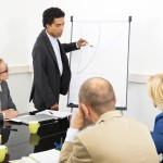 trainer provides explanation of an in-company workshop, standing